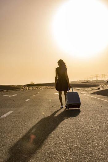 Woman walking with luggage on rural road in the desert with a car coming in the oposite side