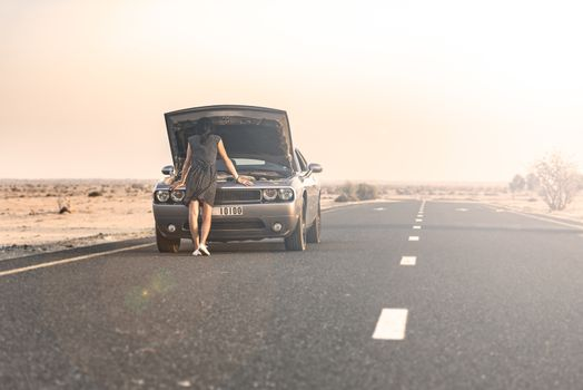 Woman looking to find the issue of the breakdown of her sport car on a road in the desert