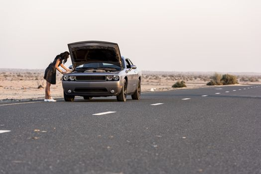 Car Breakdown with Woman checking the engine in the road in the middle of the desert
