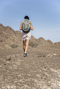 Woman trekking in a Wadi (Dry mountains) of Showka, Ras Al Khaimah, United Arab Emirates