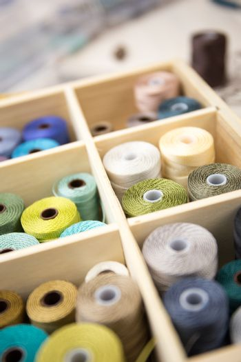 Lifestyle concept, work from home to reinvent your life: close-up detail some colored thread spools in a wooden organizer box with compartments