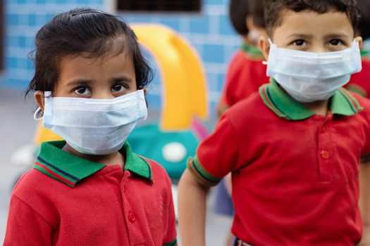 Little kids at school with medical face mask looking at camera - concept of kids using mask to protect from covid-19 or coronavirus spreading.