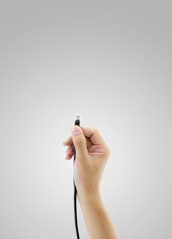 A LAN connector in hand on white background.