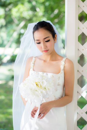 bride in a dress standing in a green garden and holding a wedding bouquet of flower.
