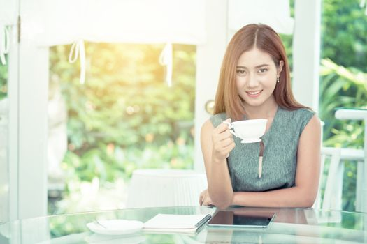 Beautiful businesswoman have enjoyed in the garden with coffee.