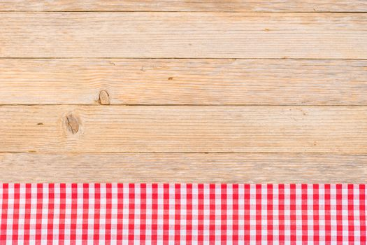 Red checked table-cloth on wooden background with copy space, top view