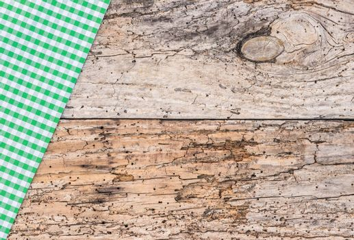 Rustic green checked tablecloth on old rustic wooden table background, copy space, top view