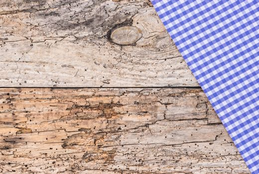 Old rustic wooden table with blue tablecloth, copy space, top view