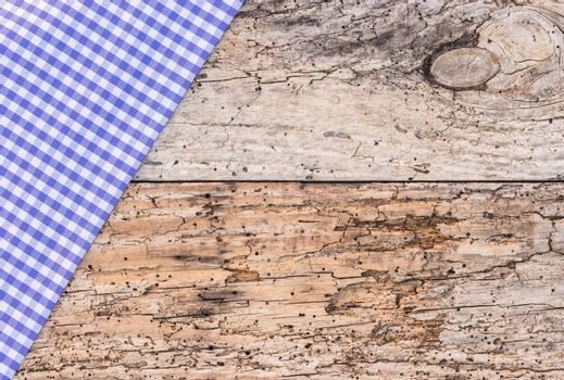 Old wooden table with rustic blue checked tablecloth, top view, copy space