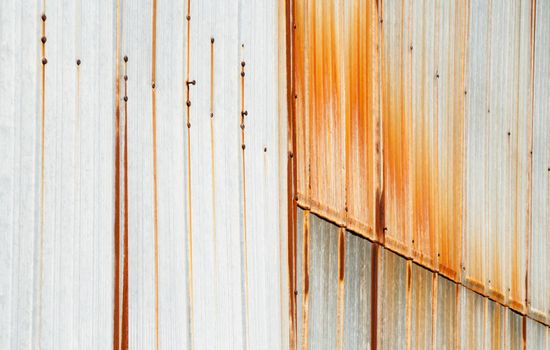 Metal siding overlapping with rust stains running down vertically from screws and rivets.