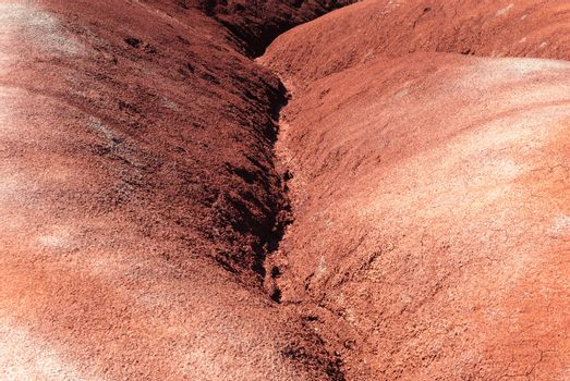 Eroded water channel between sedimentary red clay badlands dunes.