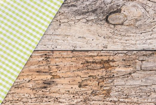 Old rustic wooden background with green checked table-cloth, copy space, top view