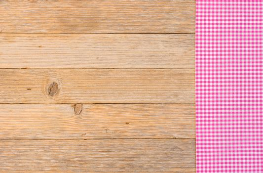 Pink checked table-cloth on wooden background with copy space, top view