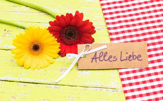 Red and yellow gerbera flowers with card with german text, Alles Liebe, means love