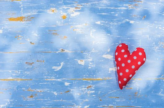 Romantic background with red love heart on blue wood with copy space
