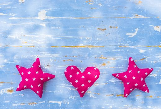Frame with stars and heart shapes on blue wooden background with copy space
