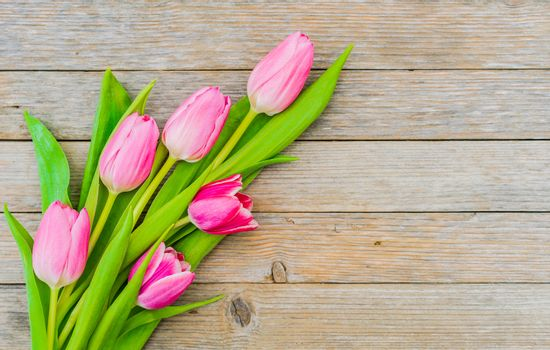 Bouquet of tulips on wooden table, top view with copy space