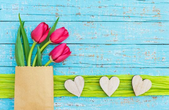 Bunch of flowers with red tulips and hearts border on blue wood with copy space