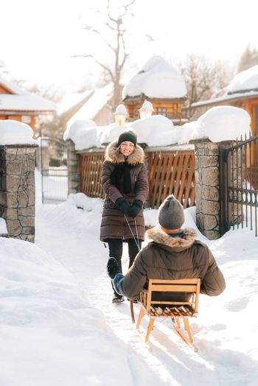 girl carries a guy on a sled on a snowy street on a sunny day