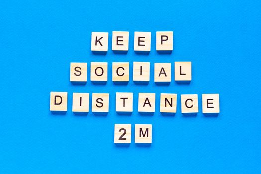 Words keep social distance 2 m. Wooden inscription on a blue background. Information sign of keep social distance 2 m from blocks. flat layout