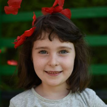Portrait of little girl among red petals on a dark green background, square image