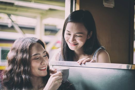 Asian women traveler have drinking a cup of coffee together with hapiness in the train at Hua Lamphong station at Bangkok, Thailand.