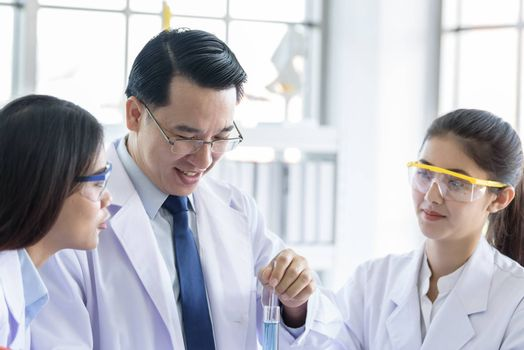 Asian senior laboratory scientist man working at lab with asian young student scientist backgroud.