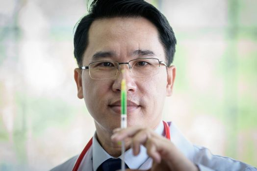 Professional asian doctor with green syringe and splashing.