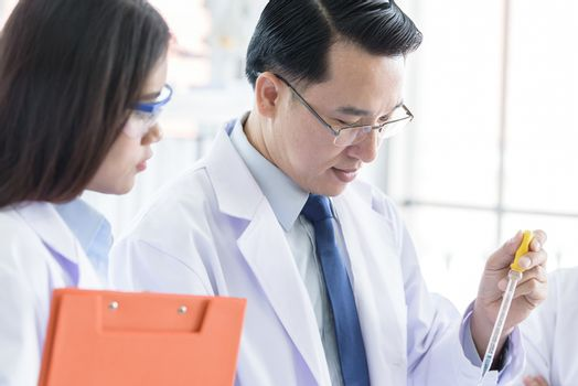 Asian senior scientist have teaching young student scientist in a laboratory.