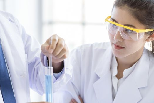 Asian yound student scientist researching  and learning with senior scientist have teaching background in a laboratory.