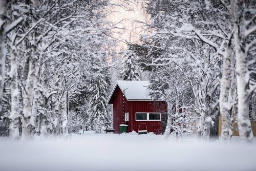 The house has covered with heavy snow and sunset time in winter season at Holiday Village Kuukiuru, Finland.