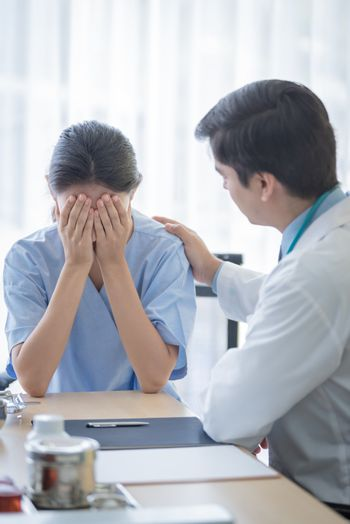 A doctor takes care of a sick patient woman with sadness and unh