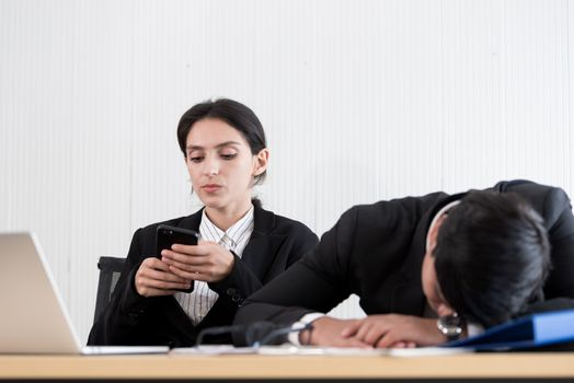 Two employees have lazy and playing the phone and sleep at the o