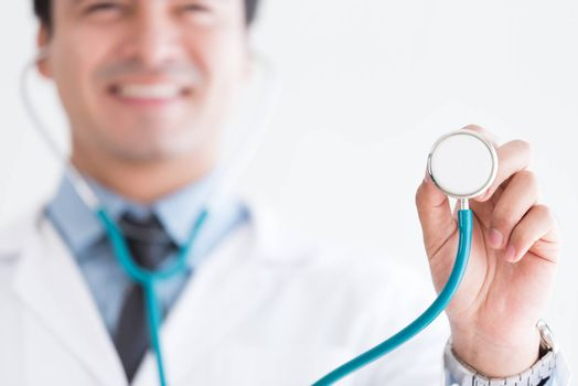 A senior doctor isolated has holding the stethoscope on white background.