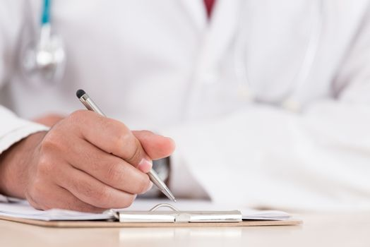 Hand of a professional doctor with silver pen over the clipboard with medical document going to make notes or prescription.