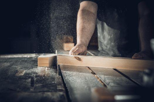 carpenter cuts wooden plank on circular saw