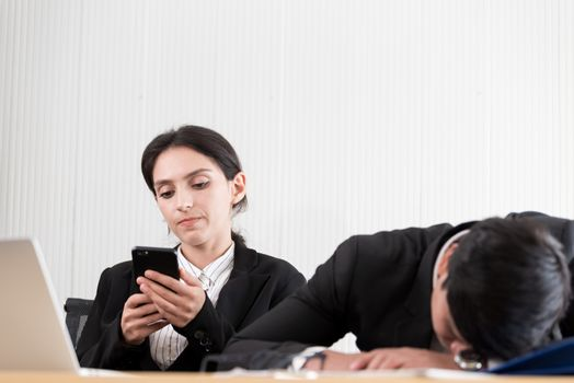 Two employees have lazy and playing the phone and sleep at the office in a relaxing time.