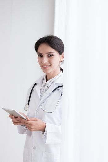 A doctor woman has to work with touching the tablet at the hospital with smiling and happiness.