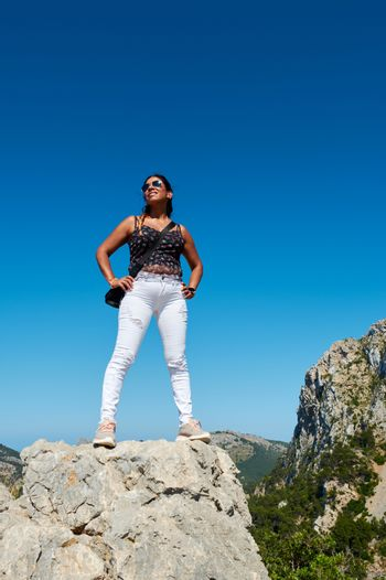 Portrait of a beautiful young hispanic latina woman, doing top conquest position, on the mountain cliff, cabo formentor, majorca,