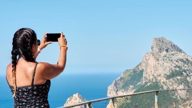 Hispanic Latina tourist woman taking photos photographer technology from smartphone devices, walking through mountains Mallorca, viewpoint Cabo de Formentor, Sierra de Tramuntana, Europe travel landscape.