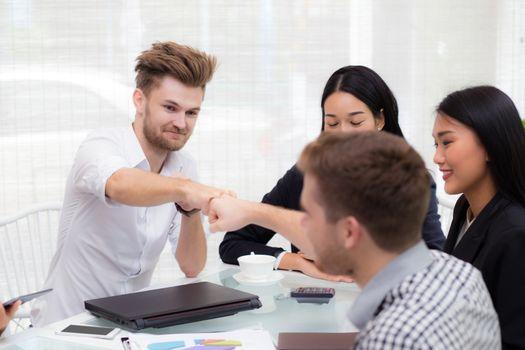 businessman giving fist bump after business achievement in meeti
