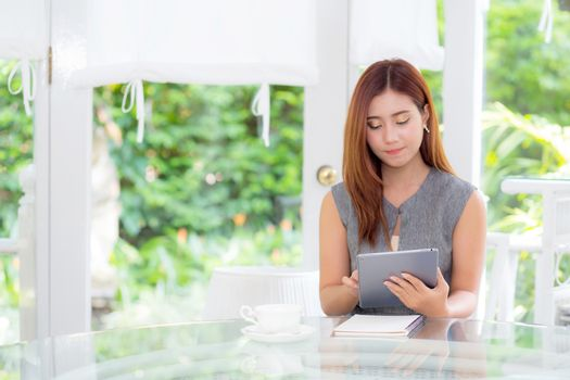 Beautiful businesswoman have enjoyed in the garden with tablet.