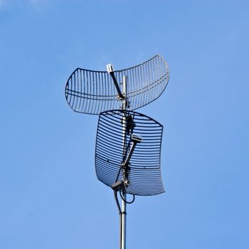 Two curved dish antennas pointing in different directions on blue sky.