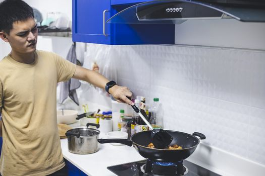 man cooking fried chicken in kitchen of home He holds spatula and pan. with gas stove that is frying thai food for family