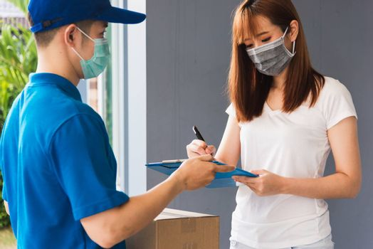 Asian young delivery man courier shopping online with package post box in uniform protective face mask coronavirus he making service woman customer using pen signature on paper book at home, COVID-19
