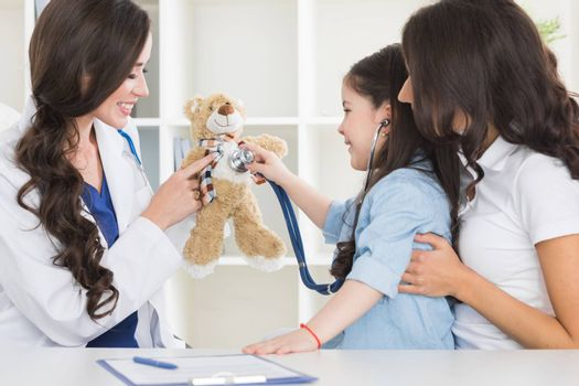Cute small child patient pretending to be doctor, holding teddy bear toy at meeting with general practitioner. Friendly nurse showing how stethoscope works to smiling little girl at checkup in clinic.