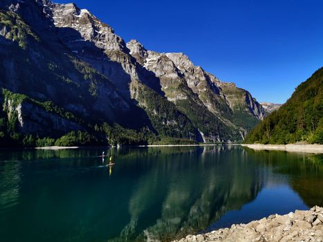 Sport and standup paddle activities on Swiss mountain lake. Outdoor lifestyle