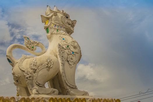 White Singha statue on temple gate of Wat Jedyod, Chiang Rai, Thailand. Wat Chet Yot is a temple that has been renovated from the remains of an ancient temple. Lion or Singha sculpture in temple,