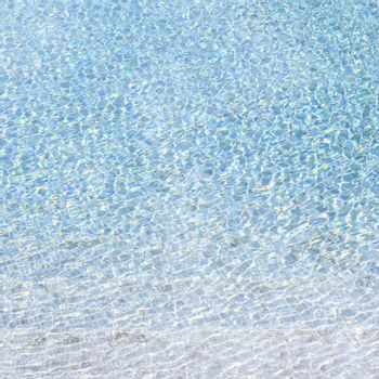 Blue swimming pool reflecting the sun rippled