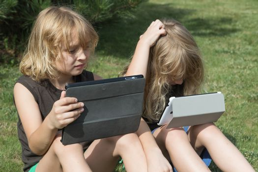 Two blond long haired boys are sitting on the lawn and are looking to the tablet. Both boys have opened their tablets. Boy sitting on the right is scratching his head by hand. All potential trademarks are removed.